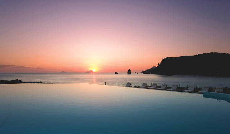 View of a pink sunset setting over the sea with the Therasia resort swimming pool in front