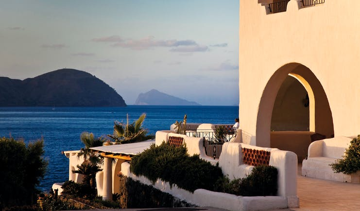 Outdoors terrace area with seats overlooking mountains and the sea