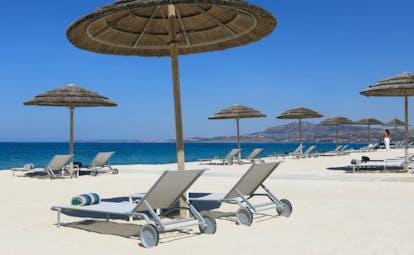 Verdura Resort white sand beach with sun beds and umbrellas