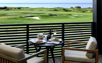 Verdura Resort balcony with two seats and view of golf course and sea