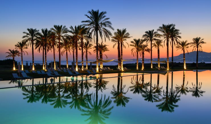 Verdura Resort evening with palm trees and swimming pool reflections