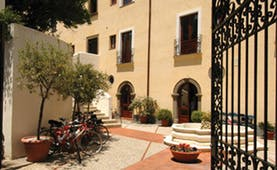 Villa Meligunis Sicily entrance iron gates patio bicycles potted plants hotel building