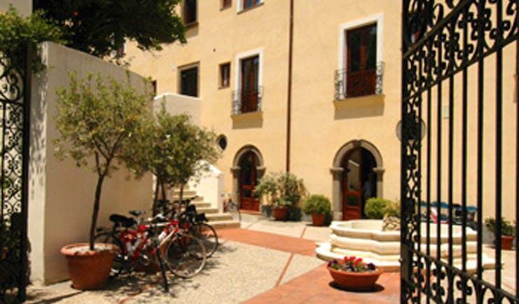 Villa Meligunis Sicily entrance iron gates patio bicycles potted plants hotel building