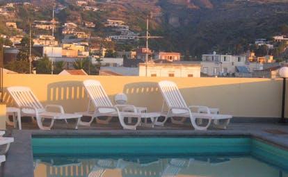 Villa Meligunis Sicily poolside sun loungers view of town