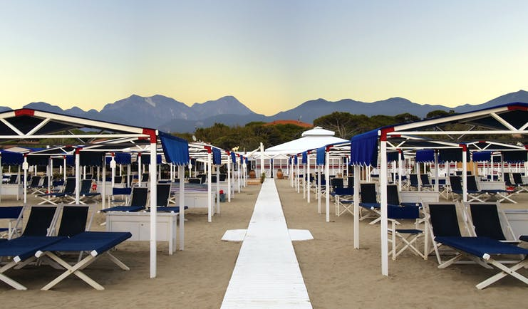 Beach with blue sunloungers and deck chairs on the sand and mountain peaks in the background