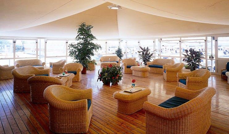 Augustus Hotel Tuscany restaurant indoor dining area wicker furniture