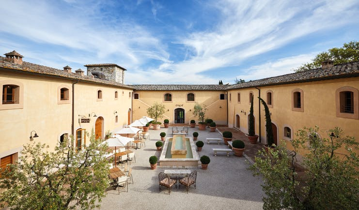 Belmond Castello di Casole Tuscany courtyard daytime outdoor seating water feature