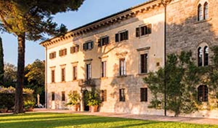 Borgo Pignano exterior of hotel building shown with lawn in front and vines growing up building