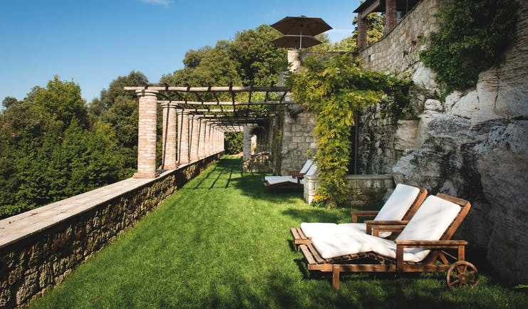 Borgo Pignano Tuscany grassy terrace outdoor seating area sun loungers