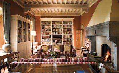 Borgo Pignano Tuscany library sofas fire bookshelves cosy décor