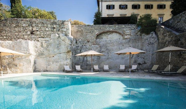 Borgo Pignano Tuscany pool sun loungers umbrellas
