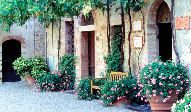Hotel Borgo San Felice Tuscany courtyard bench flowers growing up wall