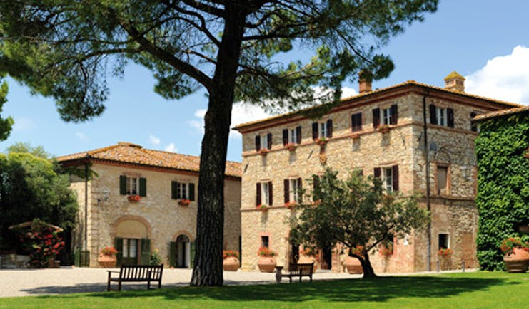 Hotel Borgo San Felice Tuscany exterior hotel building lawns trees benches