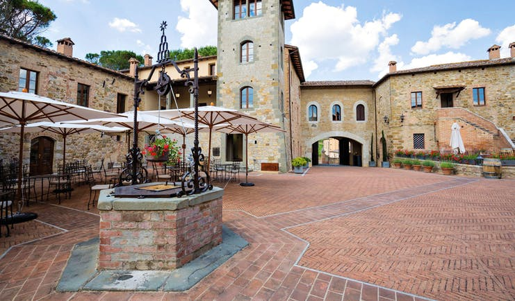 Castel Monastero Tuscany courtyard outdoor seating area surrounded by buildings