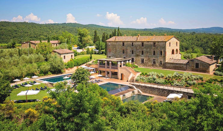 Castel Monastero Tuscany exterior shot pools hotel buildings surrounding countryside