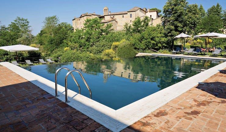 Castel Monastero Tuscany infinity pool sun loungers umbrellas