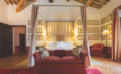 Double room with a large double bed, a pink colour scheme, sofa, and paintings hanging on the walls