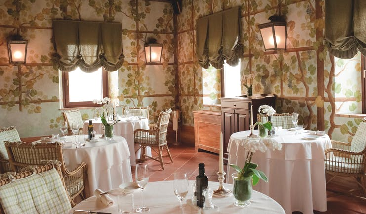 Castello banfi il borgo restaurant called the Sala dei Grappoli with circular tables set up around the room with pink table cloths