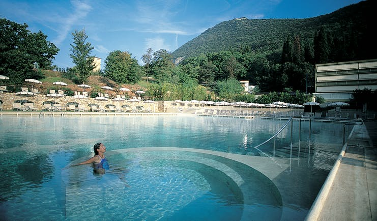 Grotta Giusti Tuscany pool sun loungers umbrellas woman in hydro massage area