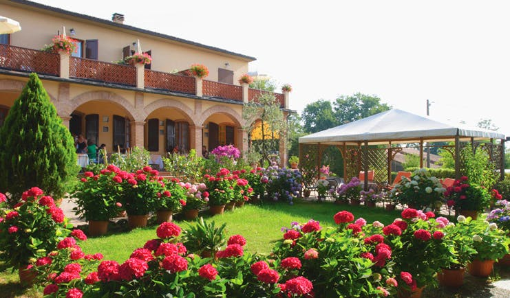 Hotel Le Renaie Tuscany lawns potted plants pink flowers hotel building in background