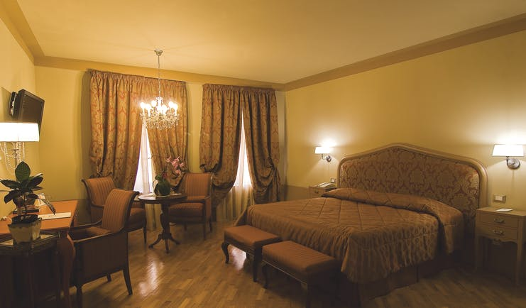 Double room at the Hotel San Luca Palace with brown and beige colour scheme, large double bed, chandelier and draping curtains