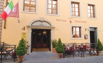 Exterior view of the entrance to the hotel with the Italian flag hanging outside and potted plants