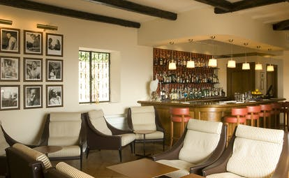 Indoor bar with photos on the wall, cushioned seats and a wood pannelled bar area with drinks behind