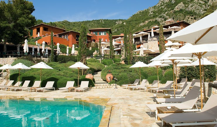 View of the hotel from the pool with sun loungers around the pool