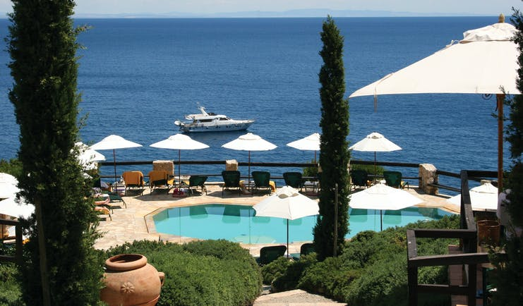 Pool and sea view with bushes and sunloungers and a boat in the sea
