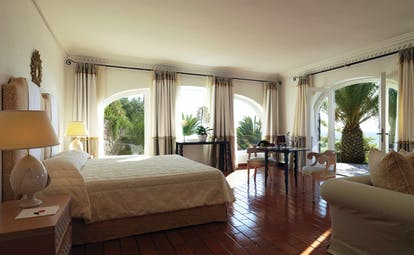 Suite with sea view, wood pannelled floors, large double bed, sofa and balcony