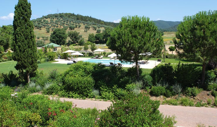 L Andana Tuscany pool sun loungers umbrellas views of countryside