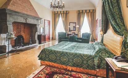 Palazzo Leopoldo Tuscany junior suite traditional décor bed seating fireplace