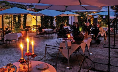 Relais dell'Orologio Pisa patio at night outdoor dining area tables chairs umbrellas candles