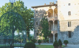 View of the exterior of the Relais La Suvera with a stone building with arched window and greenery outside