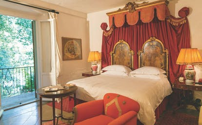 Farmhouse room at the Relais la Suvera with a large double bed, red armchair and double doors opening onto a balcony