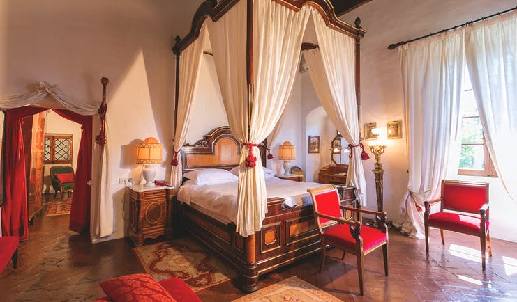 Fox suite at the Relais la Suvera with a large wooden bed with white drapes, a white and red colour scheme with red chairs around the room