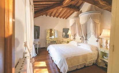 Junior suite in the Relais la Suvera with white and cream decorations with a wooden ceiling, large bed and vanity mirror