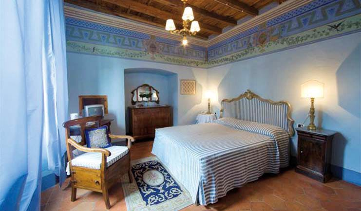 Bedroom with double bed, blue colour scheme and chandelier