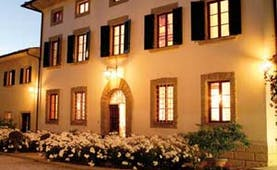 Exterior of hotel with white flowers infront, shutters on windows and wall lamps glowing