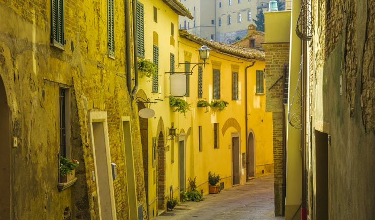 Narrow shady street with yellow golden stone buildings with small windows in Montepulciano Tuscany