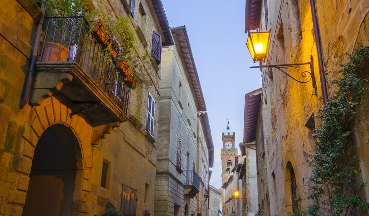 Narrow street at dusk with lamps on sides of houses in Pienza Tuscany