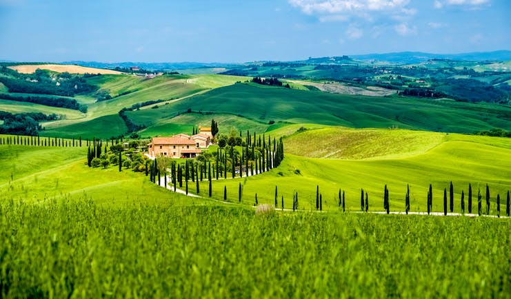 Green hills with cypress trees and orange coloured farmhouse in Tuscany