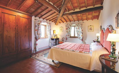 Bedroom with wood pannelled ceilings and floors, floral patterned curtains and double bed