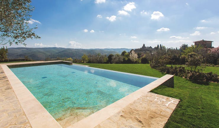 Heated infinity pool in travertine marble looking out over grassy mountains and trees