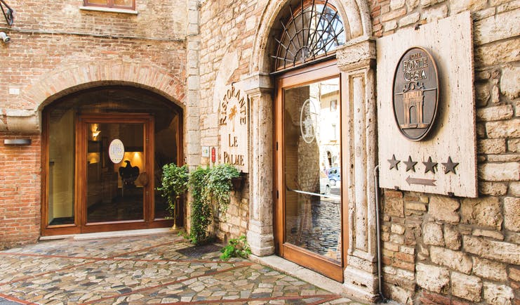 Hotel fonte cesia entrance with stone walls and big archway for door