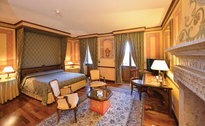 Hotel Fonte Cesia suite with large double bed, fireplace, desk and armchairs