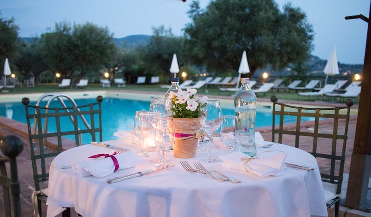 Table set with white cloth and candles at side of pool in evening