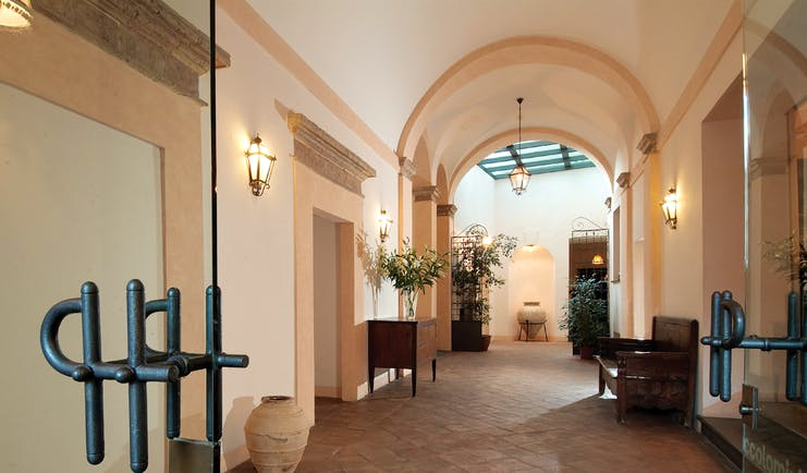 Entrance to hotel with large archway and wall lamps lighting the way