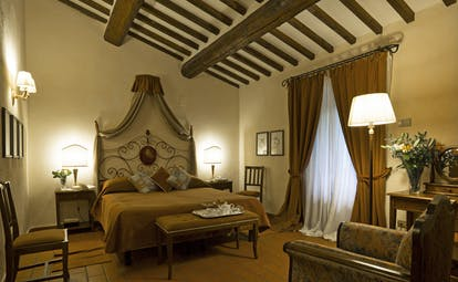 Bedroom at the Hotel Villa di Monte Solare with a large bed, draped brown curtains and a brown colour scheme