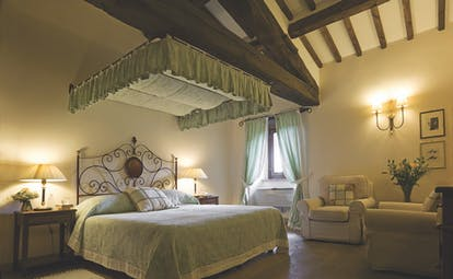 Bedroom at the Hotel Villa di Monte Solare with a large bed, armchairs and green and cream colour scheme